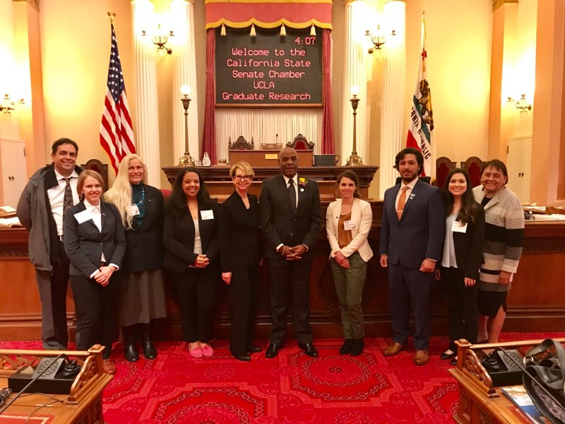 On the floor of the California Senate Chamber. From left to right: Chaitanya Komanduri of UCLA government relations, Shover, Ettner, Keeney-Parks, Garrell, California State Senator Steven Bradford, Rith-Najarian, Gonzalez, Brice, and Ramona Cortés Garza of UCLA Government Relations.