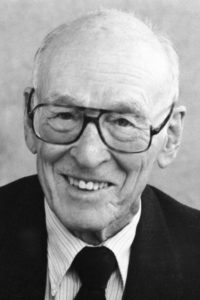 A black and white photo of Paul Boyer, Nobel Prize winner in Chemistry and professor at UCLA. Boyer is smiling at the camera.